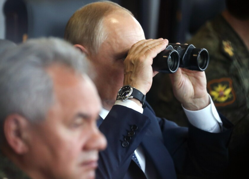 Russian President Vladimir Putin, center, watches through binoculars as Russian Defense Minister Sergei Shoigu sits near during the joint strategic exercise of the armed forces of the Russian Federation and the Republic of Belarus Zapad-2021 at the Mulino training ground in the Nizhny Novgorod region, Russia, Monday, Sept. 13, 2021. The military drills attend by servicemen of military units and divisions of the Western Military District, representatives of the leadership headquarters and personnel of military contingents of the armed forces of Armenia, Belarus, India, Kazakhstan, Kyrgyzstan and Mongolia. (Sergei Savostyanov, Sputnik, Kremlin Pool Photo via AP)