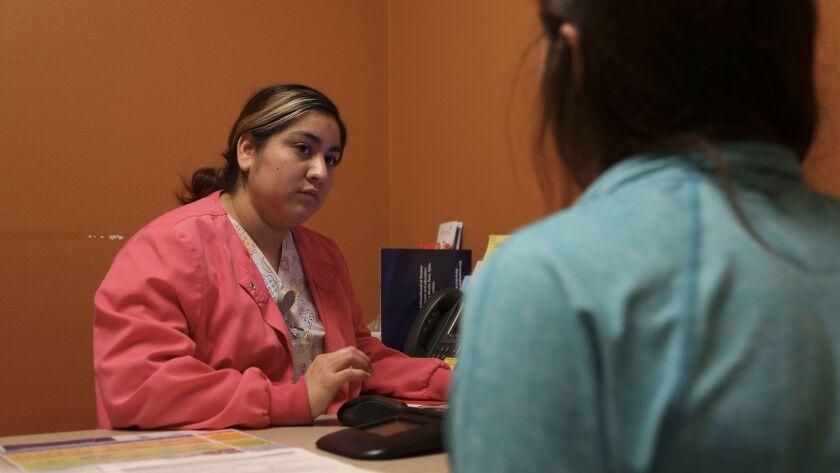 Lilibeth Juarez, a Planned Parenthood health center senior assistant, speaks with a patient about bi