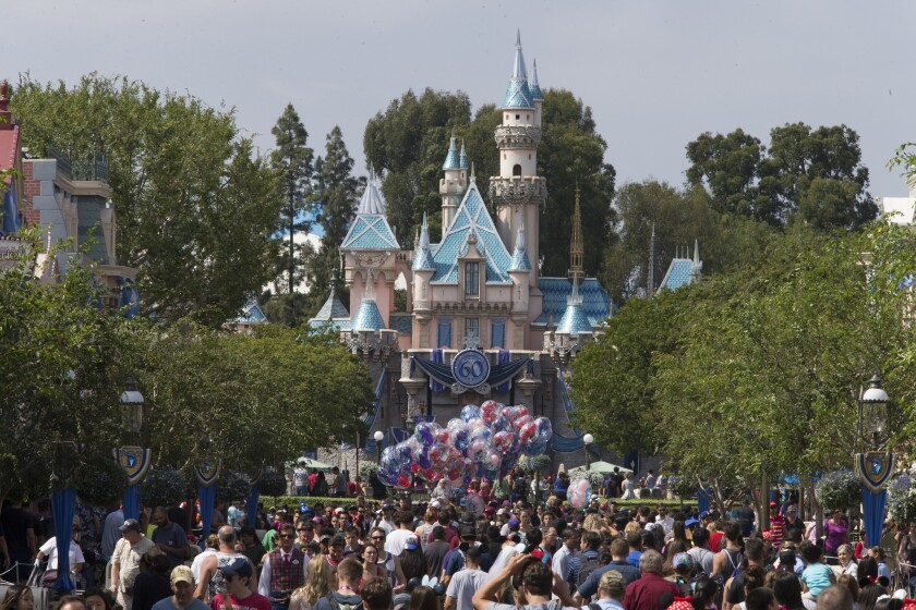 A large crowd strolls down Disneyland's Main Street on its 60th anniversary in June.