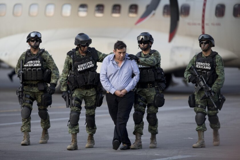 """Varios soldados escoltan a Omar Treviño Morales, alias el """"Z-42″, líder del cártel de narcotraficantes de Los Zetas, mientras es trasladado de un avión militar a un vehículo en el hangar de la Procuraduría General de la República en la Ciudad de México, el miércoles 4 de marzo de 2015."""