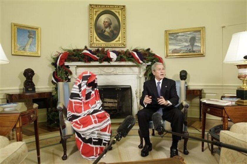 President George W. Bush meets with Darfur human rights activist Dr. Halima Bashir, left, Wednesday, Dec. 10, 2008, in the Oval Office of the White House in Washington. (AP Photo/Evan Vucci)