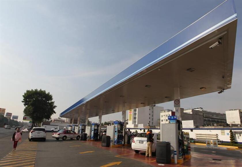 Empleados de gasolineras que se encuentran parcialmente con su servicio, despachan combustible este viernes en Ciudad de México (México). EFE