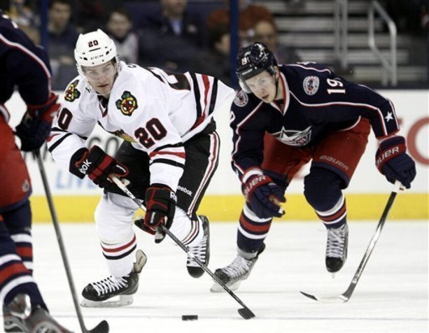 Chicago Blackhawks' Brandon Saad, left, carries the puck in front of Columbus Blue Jackets' Ryan Johansen during the first period of an NHL hockey game in Columbus, Ohio, Thursday, March 14, 2013. (AP Photo/Paul Vernon)