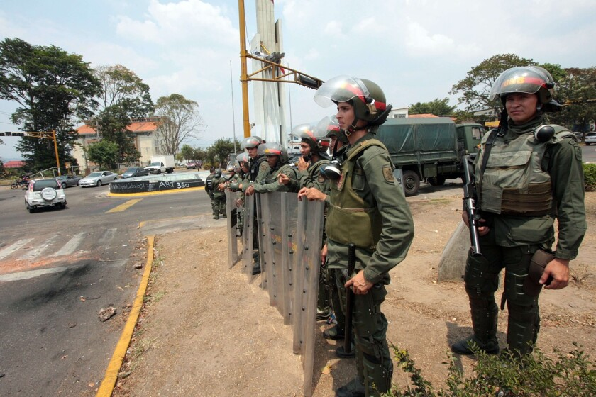Security forces stand guard in the streets of San Cristobal, Venezuela, after barricades set up by antigovernment demonstrators were cleared. Protests driven in part by food shortages have roiled Venezuela for two months.