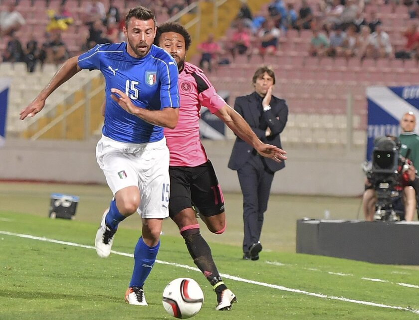 Italy's Andrea Barzagli, left, vies for the ball with Scotland's Ikechi Anya during a friendly match between Italy and Scotland, in preparation for the upcoming Euro 2016 European Championships, at the Ta' Qali stadium in Attard, Malta, Sunday, May 29, 2016. (AP Photo/Rene Rossignaud)