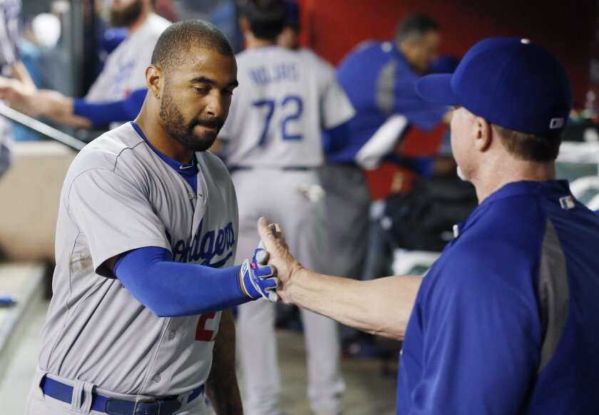 Matt Kemp, left, slaps hands with Mark McGwire in the dugout prior to a baseball game against the Arizona Diamondbacks Wednesday, Aug. 27, 2014, in Phoenix. (AP Photo/Ross D. Franklin)