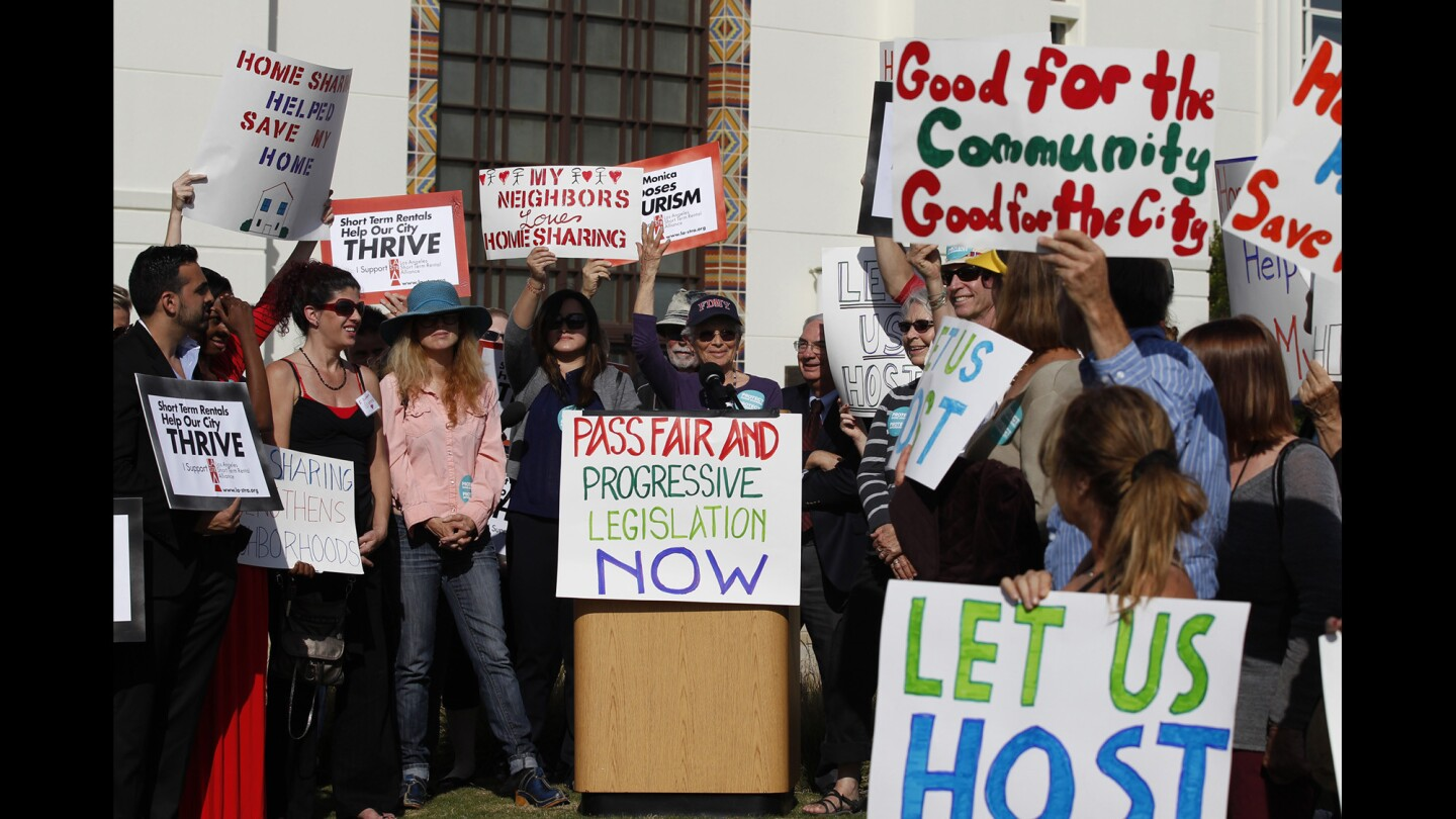 Airbnb supporters listen to Airbnb host Arlene Rosenblatt speak during a rally outside the Santa Monica City Council as they are set for a second and final vote on regulations that would outlaw most short-term rentals in the beach city.