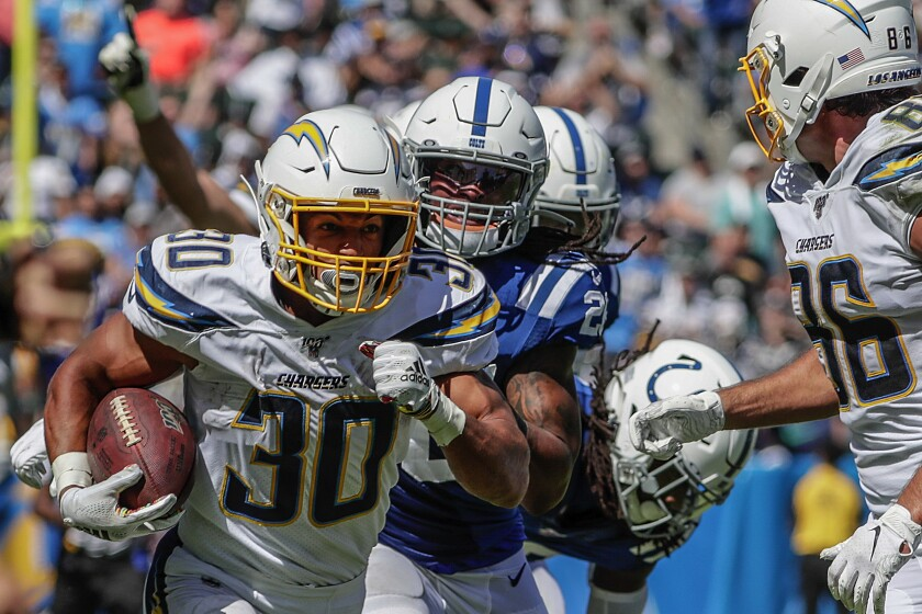 The Chargers' Austin Ekeler rushes the football against the Colts.
