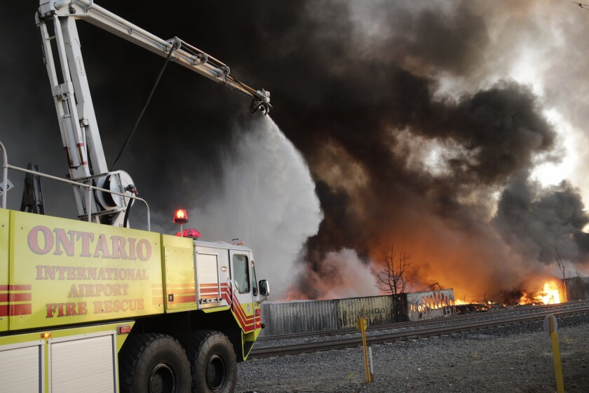 Ontario International Airport fire crews battle the fast-moving fire at a recycling center.