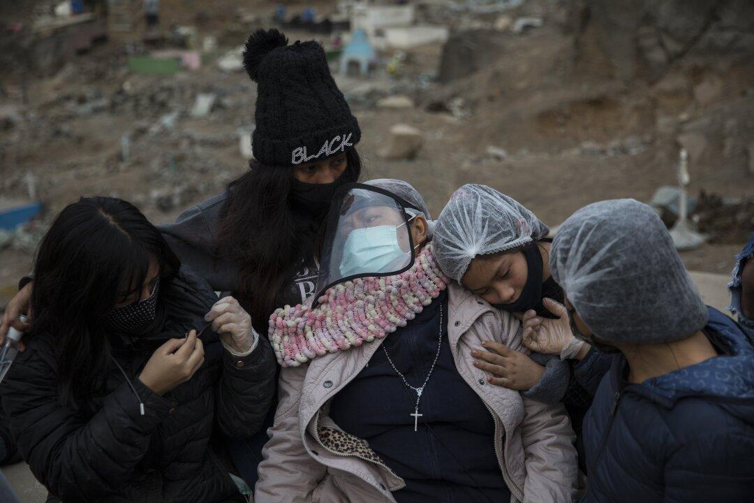 Relatives hug Aurora Davila as she buries her son Ronald Palomo, who died of COVID-19.
