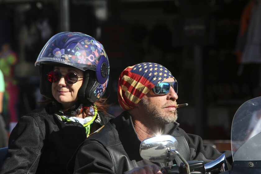 Two people ride down Main Street in Daytona, Fla., during the start of Bike Week on Friday, March 5, 2021. (Sam Thomas /Orlando Sentinel via AP)