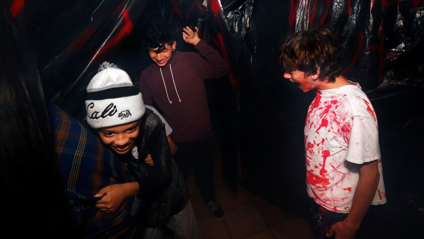 Oswaldo Corado, 12, left, and Carlos Zevallos, 16, are harassed by performer Sebastian Foster, 13, as they make their way through haunted maze.