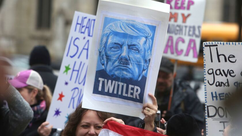 A demonstrator holds up a sign comparing Donald Trump to Hitler at a protest march in Philadelphia on Jan. 26.
