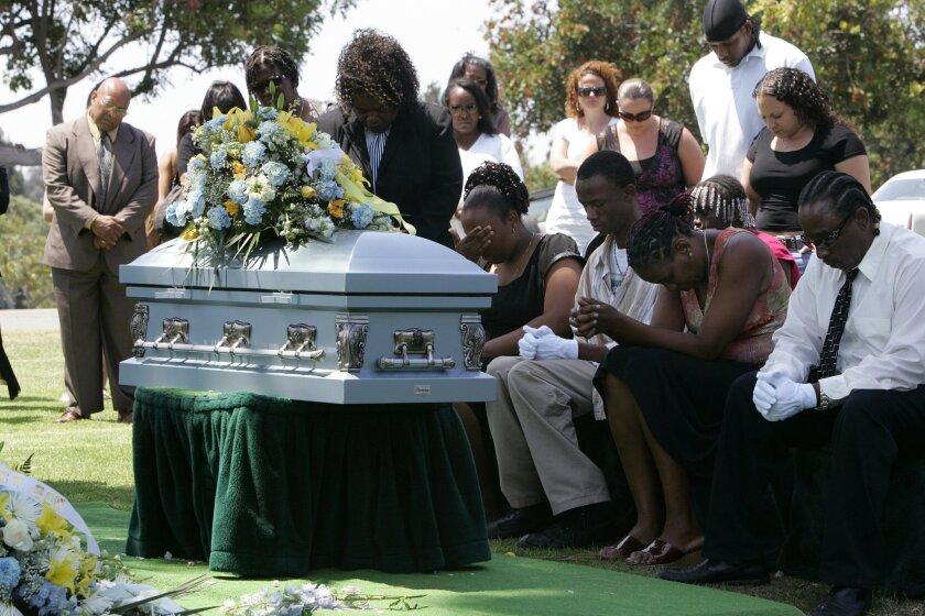 Family members bury Malachi Roberts-McBride following a funeral.