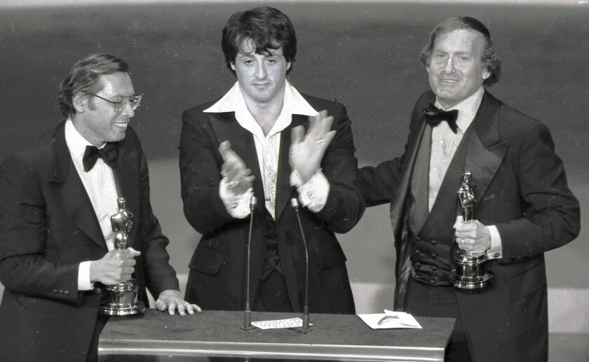 """Irwin Winkler, left, and Robert Chartoff, right, flank Sylvester Stallone after receiving Golden Globes in 1977 for """"Rocky."""""""