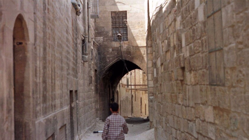 A boy cycles through the narrow alleys of the old city of Aleppo, north of Damascus, Syria, in June 1998.