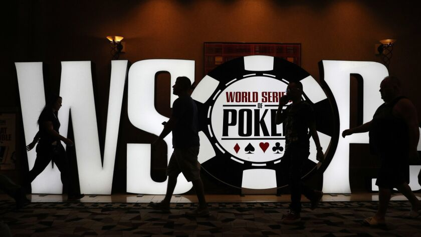 People walk by a sign during the first day of the World Series of Poker main event Monday, July 2, 2