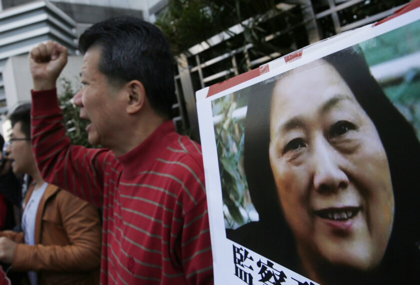 Anti-Beijing protesters hold a picture of Chinese journalist Gao Yu at a rally outside the Chinese central government's liaison office in Hong Kong.