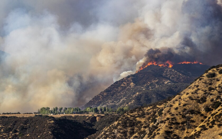 Flames scorch a ridge overlooking homes as the Apple fire burns Sunday in Cherry Valley.