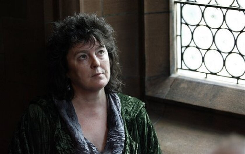 """Writer and poet Carol Ann Duffy poses for photographs at John Rylands Library in Manchester, England, Friday, May 1, 2009, after being named as Britain's poet laureate - the first woman to hold a post that has been filled by William Wordsworth, Alfred, Lord Tennyson and Ted Hughes. A witty and popular writer whose work is widely taught in British schools, Duffy is also the first openly gay laureate. Duffy said she had thought """"long and hard"""" before accepting the job, which now has a 10-year term.(AP Photo/Paul Thomas)"""