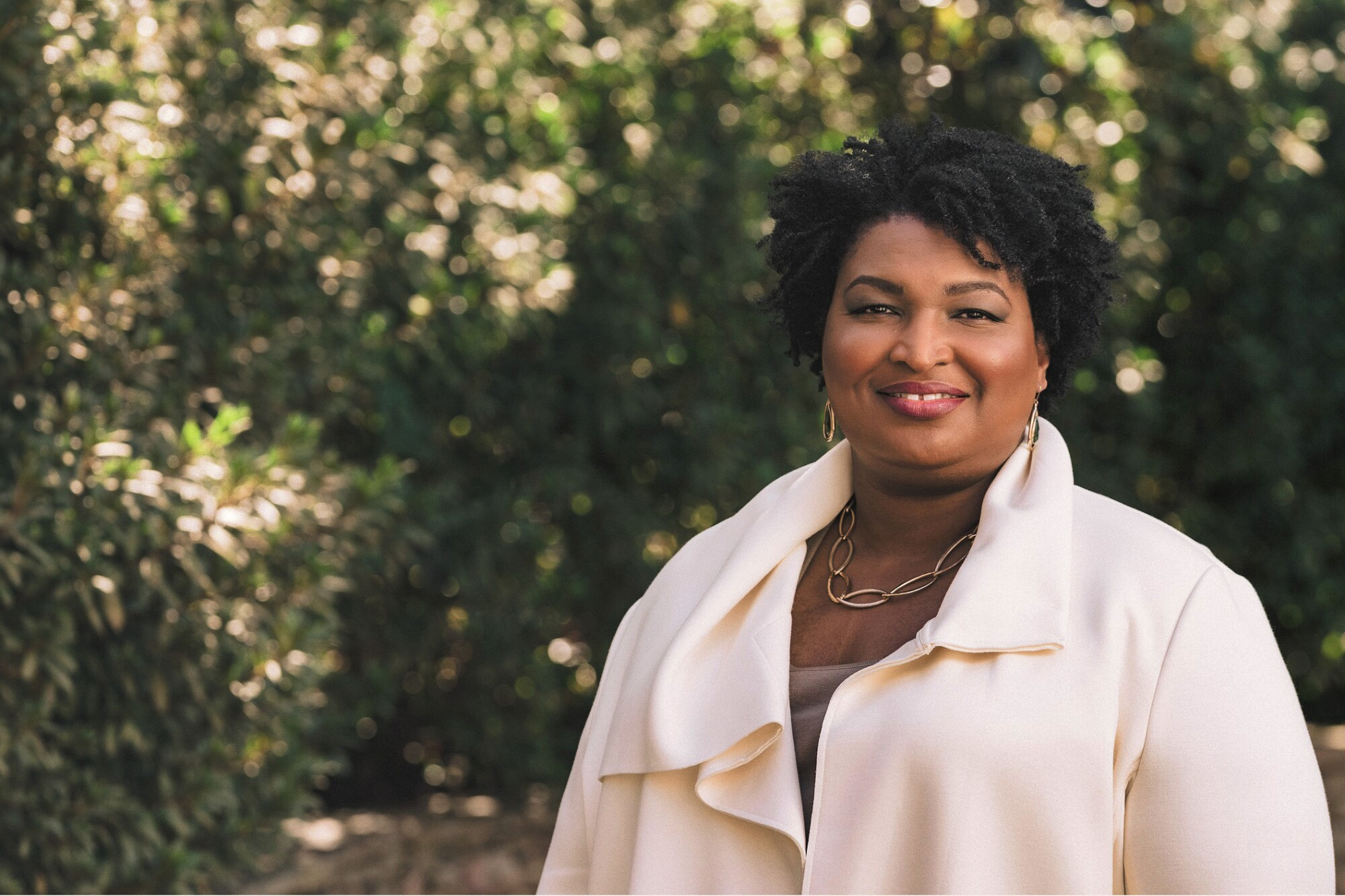 Stacey Abrams  smiles while standing in front of a group of trees and bushes.