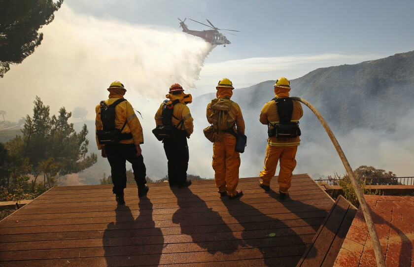 Firefighters watch a helicopter drop water on a brush fire in Pacific Palisades