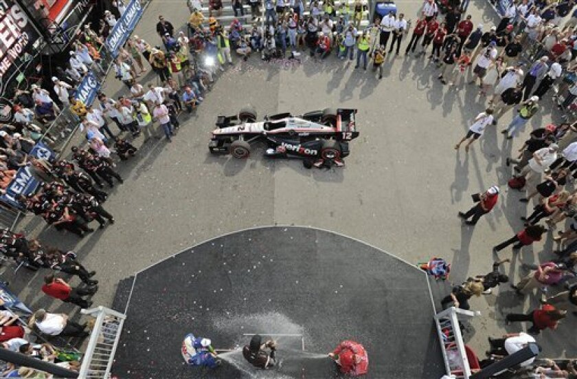 Second-place Scott Dixon, right, of New Zealand, and third-place Helio Castroneves, of Brazil, spray champagne on race winner Will Power, of Australia, after the IndyCar Series' Indy Grand Prix of Alabama auto race at Barber Motorsports Park on Sunday, April 1, 2012, in Birmingham Ala. (AP Photo/The Birmingham News, Bernard Troncale) MAGS OUT