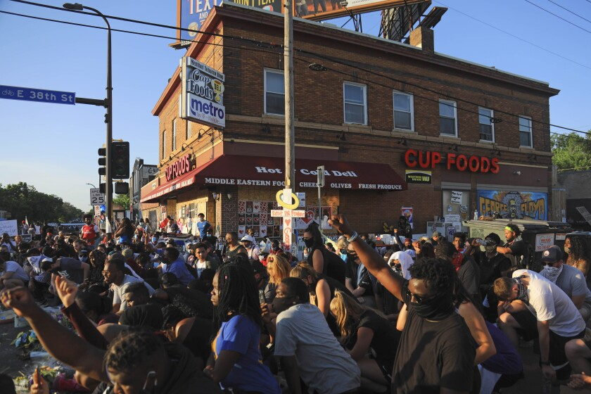 In this June 1, 2020, photo, people gather near the Cup Foods grocery store where George Floyd died in Minneapolis. Floyd was accused of using a fake $20 bill to buy cigarettes from the grocery store. His story is similar to that of other African Americans who died at the hands of police over minor offenses. (AP Photo/Bebeto Matthews)
