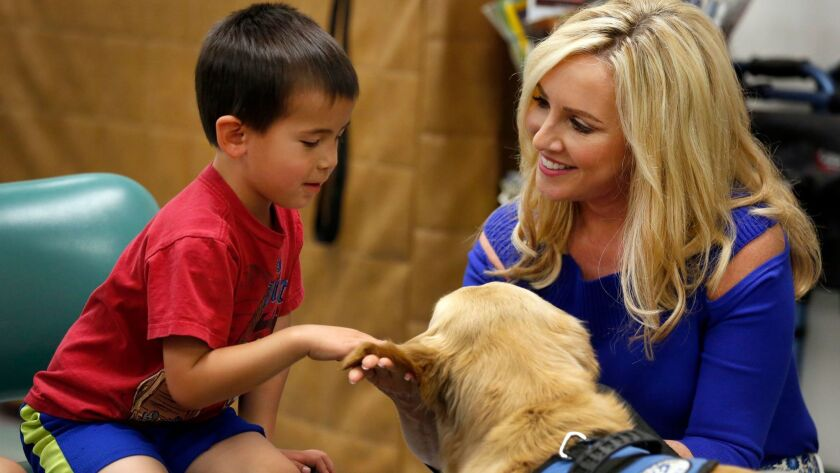 Jamie Colby, right, introduces therapy dog Bailey to Michael Meehan, 4, during a program at St. Paul's Senior Services Center and St. Paul's Childcare in San Diego. Colby, a longtime host for Fox television, is one of the newest trained handlers for Love on a Leash.
