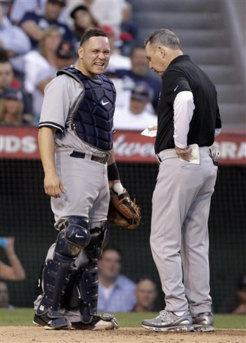 New York Yankees trainer Gene Monahan, right, tends to catcher Russell Martin during the third inning of a baseball game against the Los Angeles Angels in Anaheim, Calif., Saturday, Sept. 10, 2011. Martin was replaced by Jorge Posada. (AP Photo/Jae Hong)