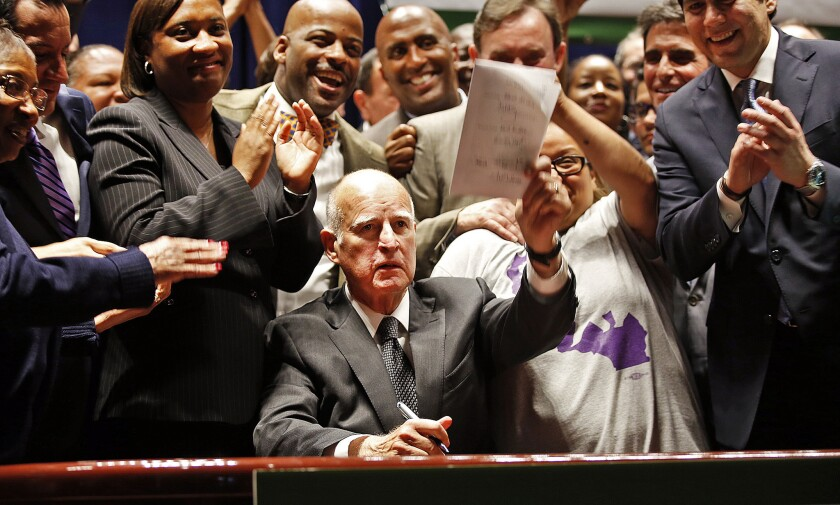 Calif. Governor Jerry Brown holds a copy of SB 3 after signing it in Los Angeles on April 4. The law makes California the first state in the nation to commit to raising the minimum wage to $15 per hour statewide.
