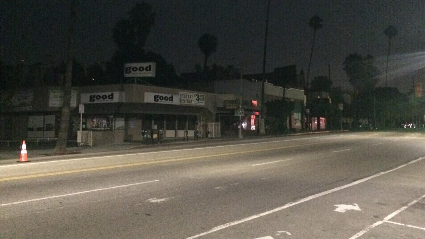 Store lights are out on Sunset Boulevard and Lucile Avenue while street lights are shining.