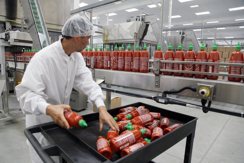 FILE - In this Oct 29, 2013 file photo, Sriracha chili sauce is produced at the Huy Fong Foods factory in Irwindale, Calif. A Los Angeles suburb is spicing up its lawsuit against this hot sauce manufacturer it claims polluted the air with pungent smells. An attorney representing the city of Irwinda