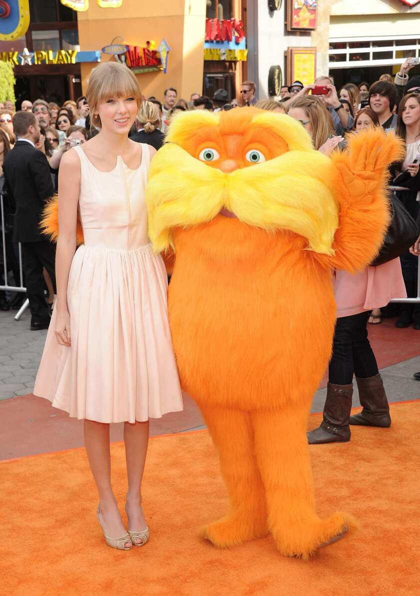 Taylor Swift stands in a pink dress with a fuzzy orange character.