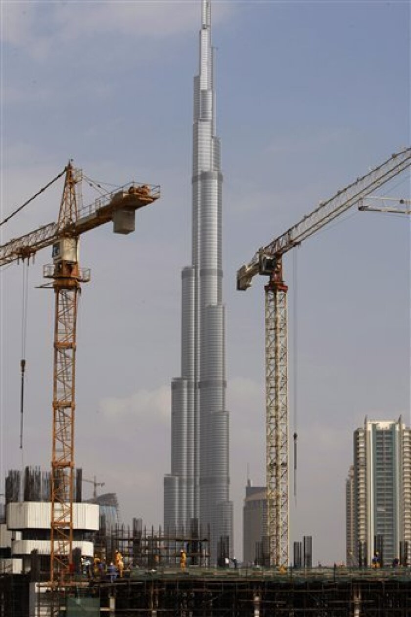 The Burj Dubai, the worlds tallest building under construction, is seen in the background as construction workers are seen at a site at the Business Bay district in Dubai, United Arab Emirates, Monday, Nov. 30, 2009. On the first day of trading since news of Dubai World's debt crunch became public,