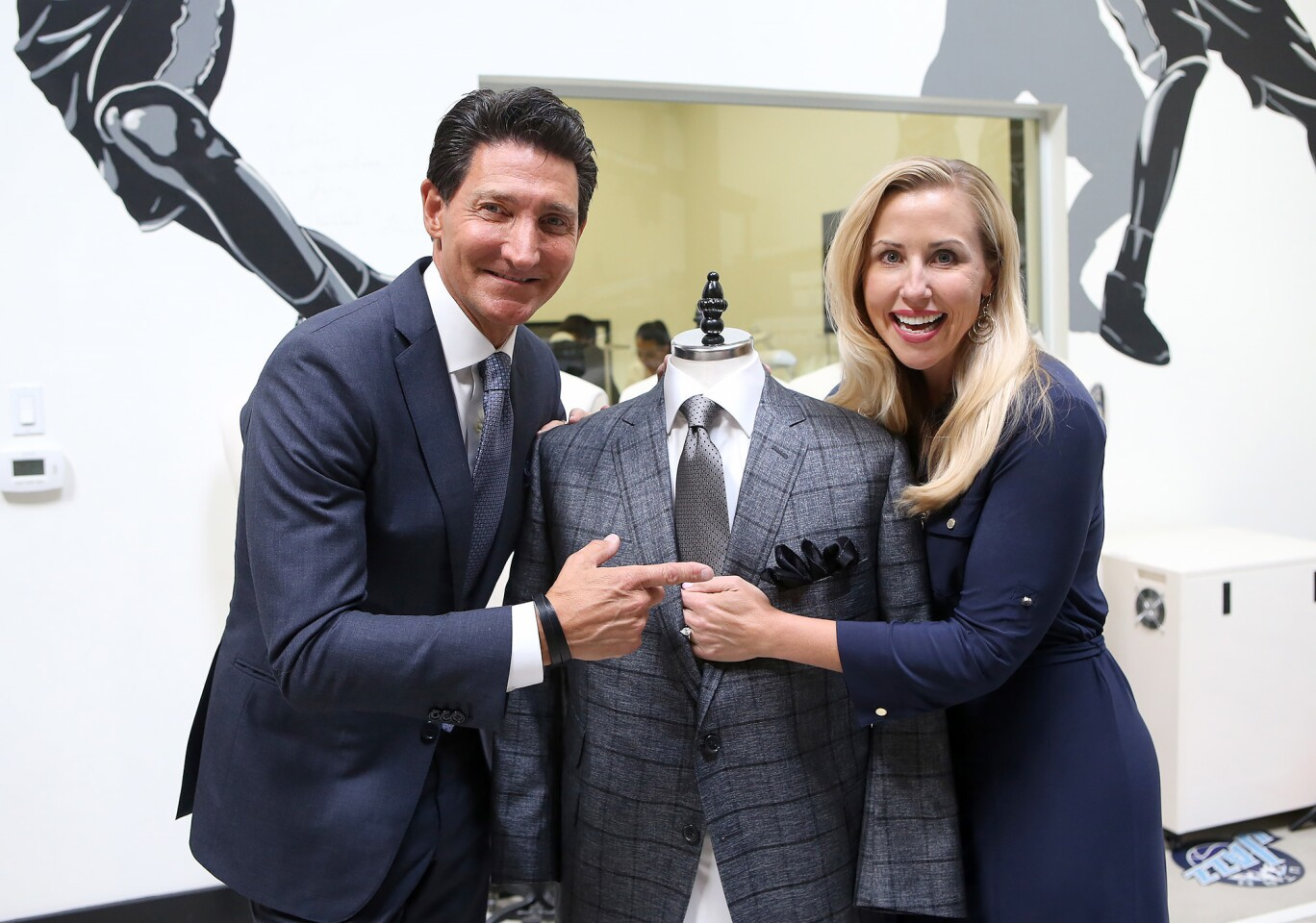 Clothier David Heil of David August, and Autumn Strier, co-founder and CEO of Miracles for Kids, dress a mannequin with one of the special ties that will benefit Strier's Tustin-based charity.