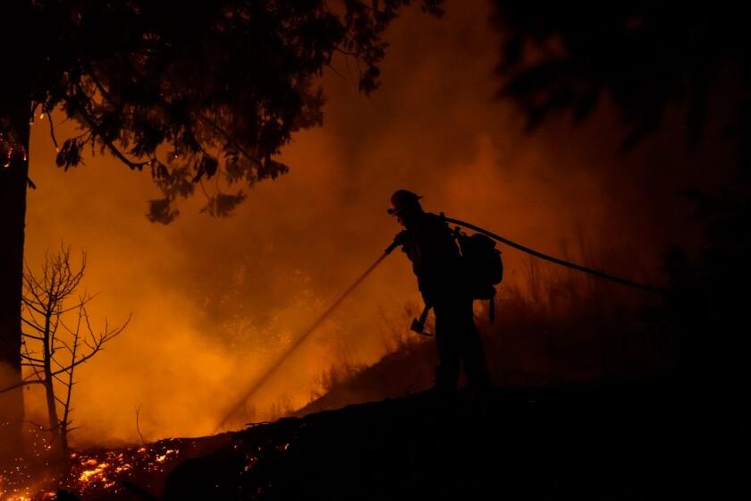 A firefighter battles the Creek Fire in Big Creek, CA.