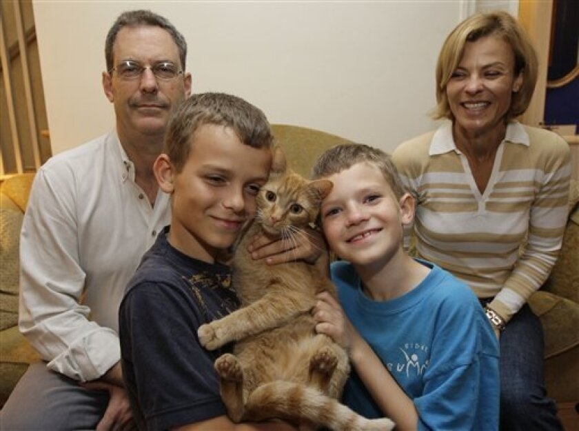 "Leo Lytel, second from right, 9, and his family David Lytel, left, Lucas Lytel, 11, and Jayne Lytel pose for a photograph with one of the family cats in their home in Washington Wednesday, May 6, 2009. Leo was diagnosed with autism as a toddler. He was undiagnosed at age 9. Provocative new research suggests that 10 percent of autistic children actually ""recover"" from the troubling developmental disorder and lose the diagnosis later on in childhood. (AP Photo/Alex Brandon)"