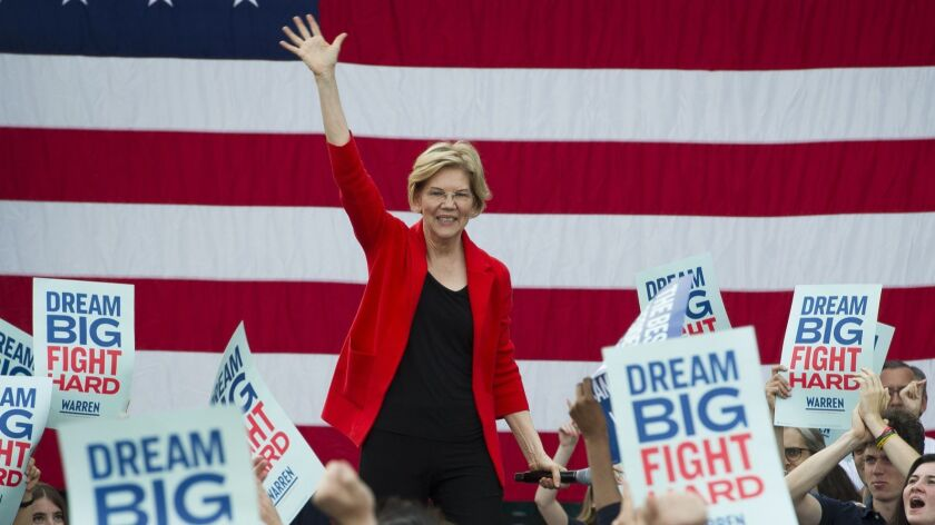 "Elizabeth Warren before an American flag backdrop. Audience members hold signs that read ""Dream Big Fight Hard."""