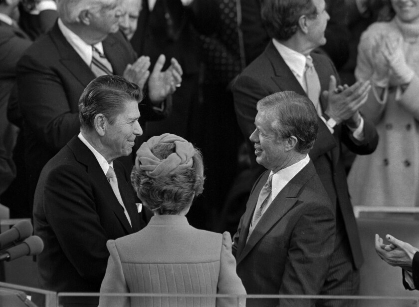 Ronald Reagan shakes hands with then-outgoing President Jimmy Carter on January 20, 1981 during Reagan's swearing in ceremony at the captiol. Reagan's wife Nancy is between them, back to camera.