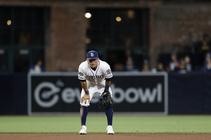 San Diego Padres second baseman Luis Urias reacts after overthrowing first base on a ball hit by Los Angeles Dodgers' Russell Martin, who was safe during the 10th inning of a baseball game Wednesday, Aug. 28, 2019, in San Diego. Enrique Hernandez scored on the play.