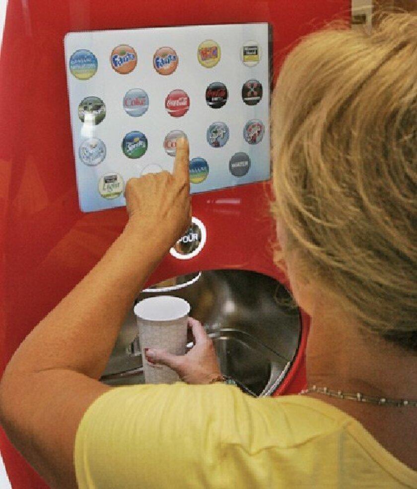 Sage Pease tried out the new Coca-Cola dispenser in Vista. (Eduardo Contreras / Union-Tribune)