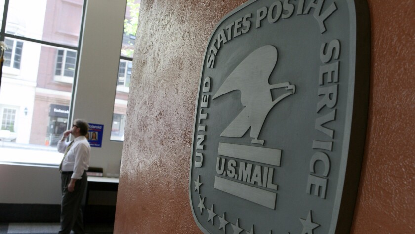 A file photo shows a man walking by a sign in the lobby of a post office.