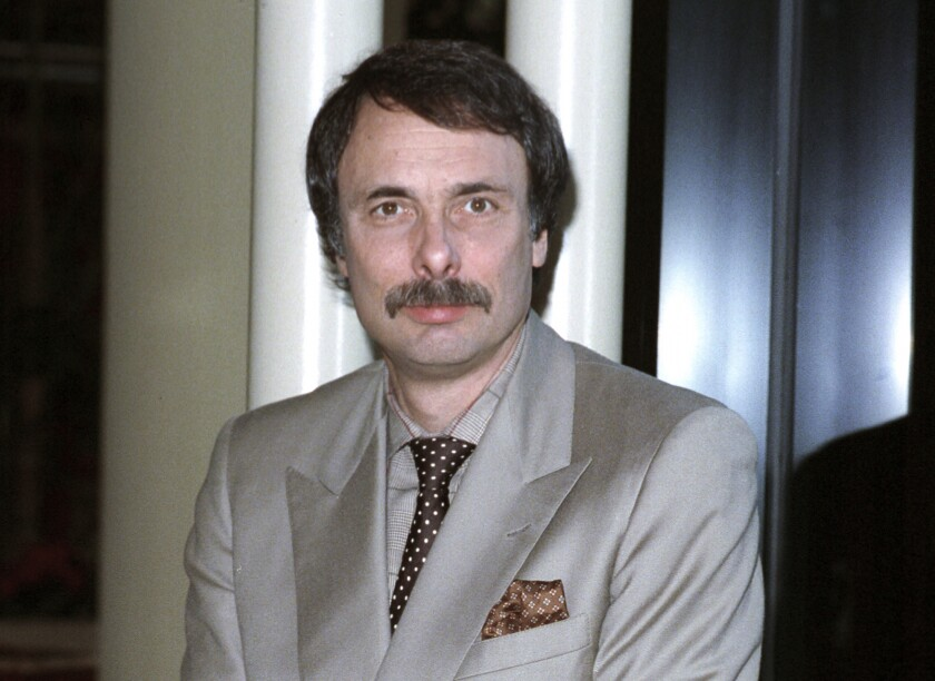 Arthur Kopit, wearing a gray suit, looks into the camera