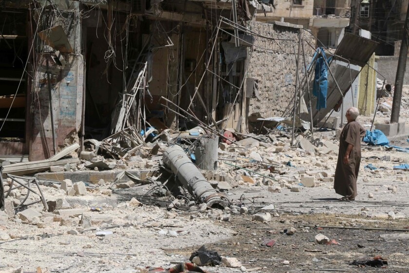 A resident of the Tariq al-Bab neighborhood of Aleppo on Aug. 16, 2016, inspects the damage caused by air raids that reportedly targeted rebel-held areas in the northern city.