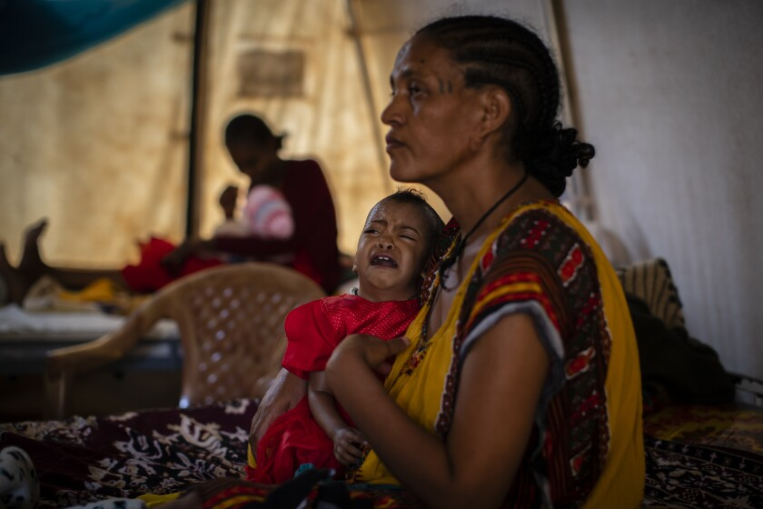 In this Tuesday, May 11, 2021 photo, Roman Kidanemariam, 35, holds her malnourished daughter, Merkab Ataklti, 22 months old, in the treatment tent of a medical clinic in the town of Abi Adi, in the Tigray region of northern Ethiopia. As the United States warns that up to 900,000 people in Tigray face famine conditions in the world's worst hunger crisis in a decade, little is known about vast areas of Tigray that have been under the control of combatants from all sides since November 2020. With blocked roads and ongoing fighting, humanitarian groups have been left without access. (AP Photo/Ben Curtis)