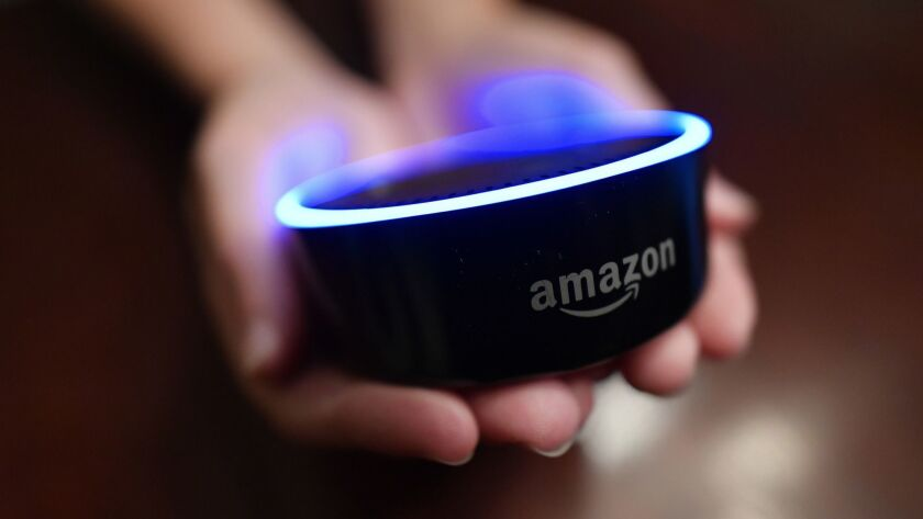 FILE - In this Aug. 16, 2018, file photo a child holds his Amazon Echo Dot in Kennesaw, Ga. Amazon m