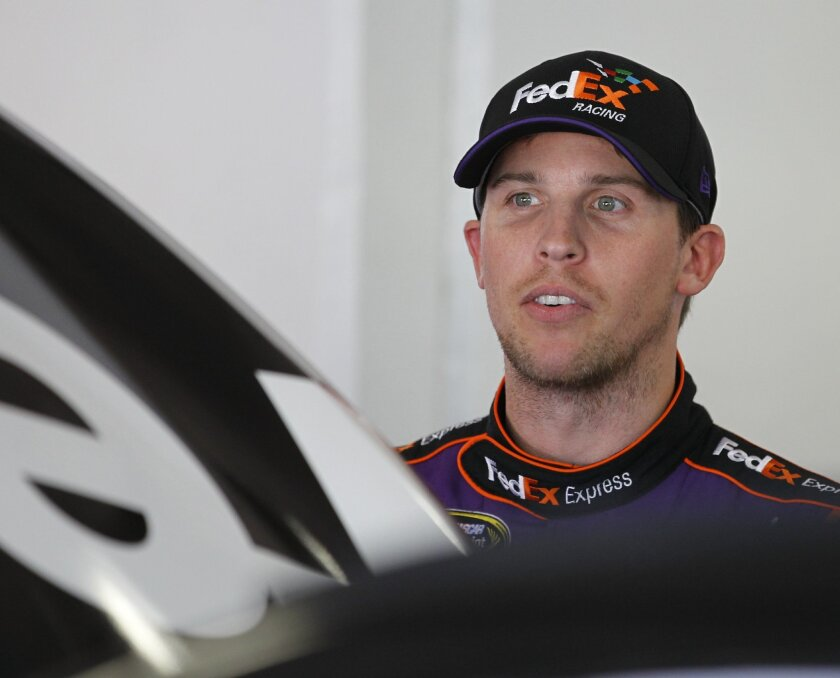 Denny Hamlin stands in his garage during a practice session for the Daytona 500 NASCAR Sprint Cup Series auto race at Daytona International Speedway, Wednesday, Feb. 18, 2015, in Daytona Beach, Fla. (AP Photo/Terry Renna)