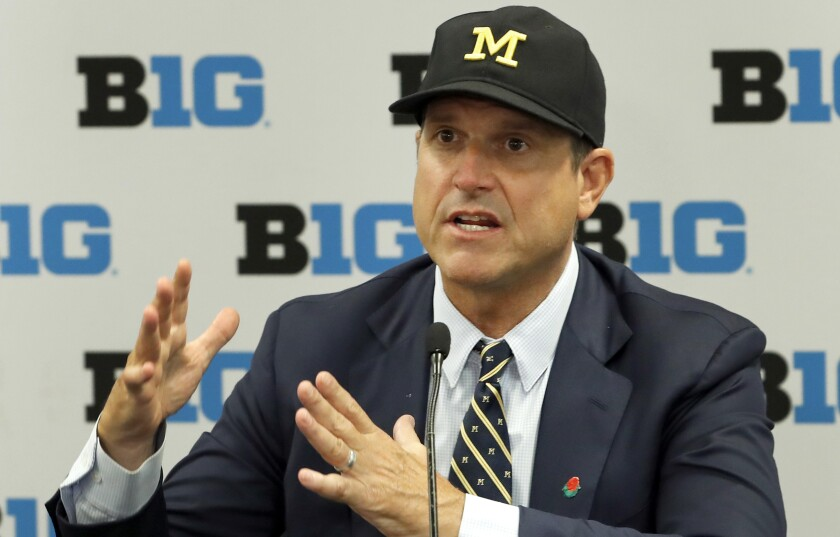 Michigan coach Jim Harbaugh responds to a question during Big Ten Conference media days in July.