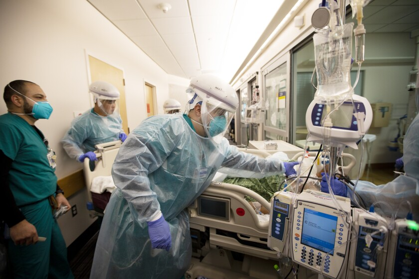 Healthcare workers in full protective gear move a critical patient in a bed through hospital hallway